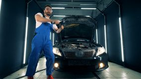 Repairman is dancing happily after fixing a car. 4K stock footage
