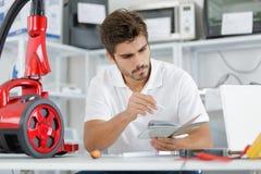 Repairman diagnosing vacuum cleaner in workshop Royalty Free Stock Photos