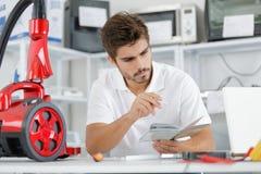 Repairman diagnosing vacuum cleaner in workshop. Repairman diagnosing vacuum cleaner in his workshop Royalty Free Stock Image