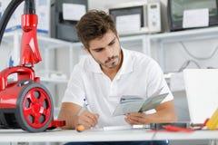 Repairman diagnosing vacuum cleaner in workshop Royalty Free Stock Photography