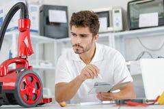 Repairman diagnosing vacuum cleaner in workshop Royalty Free Stock Image