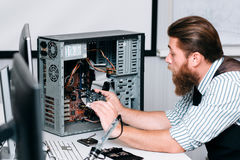 Repairman disassembling computer unit for repair. Bearded man taking electronic component out of CPU. Renovation, fix, construction concept Stock Photography