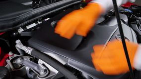 Mechanic Disassembling the Engine Cover of a Car stock video footage