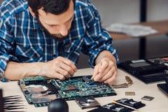Repairman disassembling laptop motherboard Stock Photography