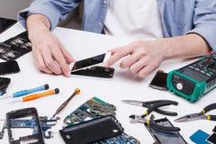 Repairman disassembling phone for inspecting Stock Photos
