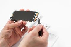 Repairman disassembling smartphone with tweezers Royalty Free Stock Images