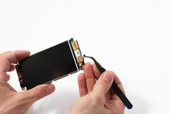 Repairman disassembling smartphone with tweezers Stock Image