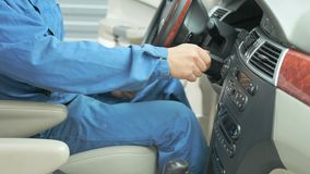 A repairman dressed in a work uniform is in the car and checks the gearbox and dashboard.  stock video