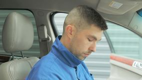 A repairman dressed in a work uniform is in the car and checks the gearbox and dashboard.  stock footage