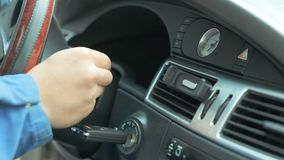 A repairman dressed in a work uniform. Is in the car and checks the gearbox and dashboard stock footage