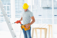 Repairman with drill machine in building. Repairman with drill machine standing by ladder in building Royalty Free Stock Photography