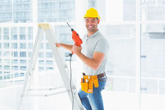 Repairman with drill machine climbing ladder in building. Portrait of repairman with drill machine climbing ladder in building Royalty Free Stock Photo