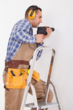 Repairman Drilling Hole In Wall Stock Photography