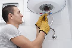 Repair electric boiler. Repairman for an electric boiler connects the wires to a thermostat royalty free stock images