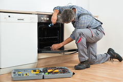 Repairman Examining Oven With Flashlight. Full length of repairman examining oven with flashlight in kitchen Royalty Free Stock Photos