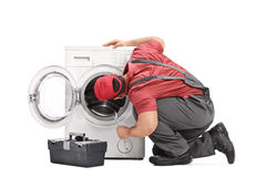 Repairman examining a washing machine. Young repairman examining a washing machine and holding a wrench isolated on white background Stock Image