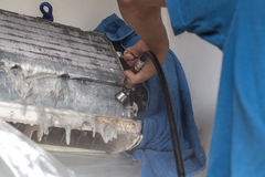 Repairman fixing and cleaning air conditioner unit Stock Photo