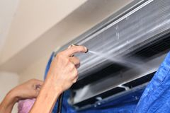 Repairman fixing and cleaning air conditioner unit. Close up Royalty Free Stock Photography