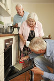 Repairman Fixing Cooker In Senior Couple's Kitchen Royalty Free Stock Photos