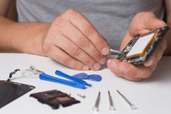 Repairman fixing disassembled smartphone with special tools and screwdrivers. concept of electronics repair devices royalty free stock photos