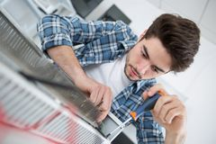 Repairman fixing gas water heater with screwdriver. Repairman fixing a gas water heater with a screwdriver stock image