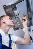 Repairman fixing kitchen extractor fan Stock Image