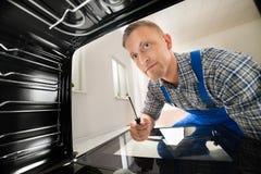 Repairman Fixing Kitchen Oven Stock Photos