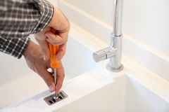 Repairman fixing a kitchen sink Royalty Free Stock Images