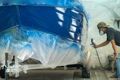 Spray gun with paint for painting a boat. Repairman fixing by painting boat body and painting boat using spray gun stock image
