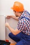 Repairman fixing radiator Stock Photos
