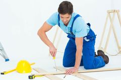 Repairman fixing screw on plank Royalty Free Stock Images