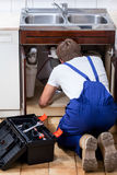 Repairman fixing the sink Royalty Free Stock Photos