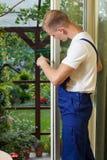 Repairman fixing a terrace door royalty free stock photography