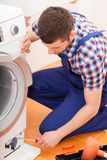 Repairman fixing washing machine Royalty Free Stock Images