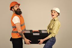 Repairman and girlfriend holding toolbox together, copy space. Smiling woman in helmet excited about renovation. Repairman and girlfriend holding toolbox Stock Photography