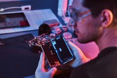 The repairman in goggles holding a damaged smartphone, looking sideways in a modern repair shop. Illumination with red. The technician in goggles holding a royalty free stock photos