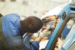 Repairman grinding metal body car. Professional repairman worker in automotive industry grinding metal body car with sparks Stock Images