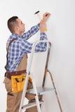 Repairman Hammering Wall With Nail Stock Photo