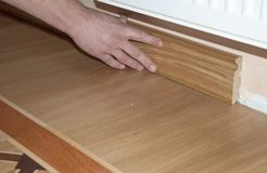 Skirting Board & Architrave. Repairman  hands Installing Skirting Board Oak Wooden Floor with Glue. Flooring and Repair. Royalty Free Stock Photos