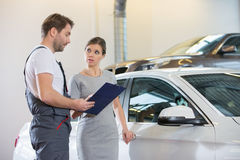 Repairman holding clipboard while conversing with female customer in automobile repair shop Stock Photography