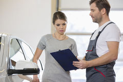 Repairman holding clipboard while conversing with female customer in repair shop Stock Photos