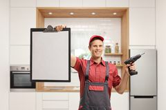 Repairman holding a drill machine and showing a blank clipboard. On white background royalty free stock image