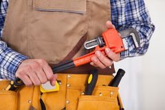 Repairman holding pipe wrench Stock Photography