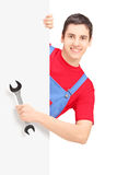 Repairman holding a wrench and posing behind a blank panel Stock Image