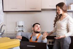 Repairman and housewife at kitchen Royalty Free Stock Photos