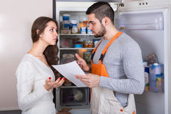 Repairman and housewife at kitchen Stock Photos