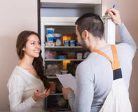 Repairman and housewife at kitchen Stock Images