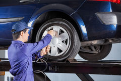 Repairman Inflating Tire Of Lifted Car Royalty Free Stock Image