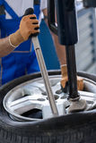 Repairman with installer replace tire on wheel Stock Photography
