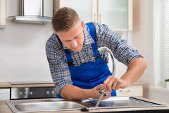 Repairman Installing Faucet Of Kitchen Sink. Young Repairman Installing Faucet Of Kitchen Sink In Kitchen Room stock photo